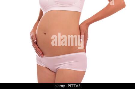 Schwangere Frau unterstützt ihren Bauch und Rücken mit ihren Händen. - Stockfoto