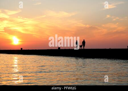 Der Mann und die Frau zu Hund am Pier in Kincardine, Ontario bei Sonnenuntergang - Stockfoto