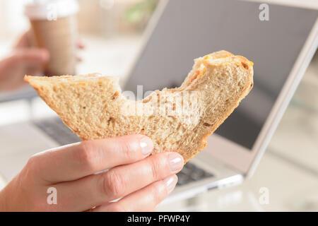 Frau essen ein Sandwich und Kaffee trinken während der Arbeit mit einem Laptop - Stockfoto