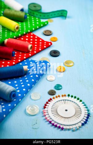 Nähzubehör und bunten Stoffen auf einem blauen Hintergrund aus Holz. Stoffen, Maßband, Pins, Buttons und Gewinde. - Stockfoto
