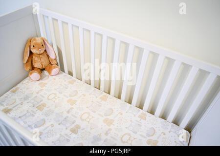 Baby Girl's Krippe. In neutralen Farben. Eule Bettlaken. Ikea SUNDVIK weiß Krippe. Wandelt in ein Kinderbett. Stofftier von Build-A-Bear Workshop. - Stockfoto