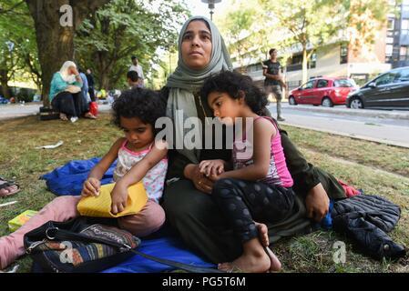 August 14, 2018 - Paris, Frankreich: Eine syrische Familie sitzen in einem öffentlichen Park in der Nähe von Porte d'Aubervilliers, wie sie für eine Wohltätigkeitsorganisation warten zu finden Not Unterschlupf für die Nacht. Die Familie der acht Mitglieder, zwei Eltern und sechs Kinder, kommen aus der Provinz Idlib und bemüht, Asyl in Frankreich für mehrere Monate im Kampf mit der Französischen Bürokratie regeln. Die 34-jährige Mutter, Kiraz Hamza, wird dargestellt mit ihren Zwillingstöchtern Fatima und Amna, im Alter von 3 und halb Jahre alt. Portrait dÕune Famille de Migranten Syriens ˆ la rue depuis Leur arrivee ein Paris, il y a Pres de huit Mois. Ils pas - Stockfoto