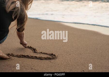 Junge Mädchen zieht ein Herz im Sand, sitzen am Strand. - Stockfoto