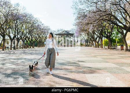 Spanien, Andalusien, Jerez de la Frontera, Frau wandern mit zwei Hunden auf Quadrat - Stockfoto