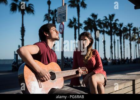 Spanien, Barcelona, Paar mit einer Gitarre sitzen auf einer Bank an der Strandpromenade - Stockfoto