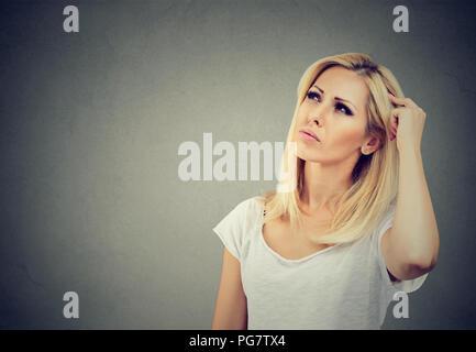 Junge nachdenkliche Frau suchen in Achtsamkeit in Memory Problem auf grauem Hintergrund - Stockfoto