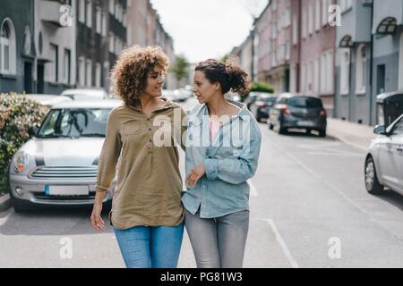 Die besten Freunde zu Fuß in die Stadt, Arm in Arm - Stockfoto