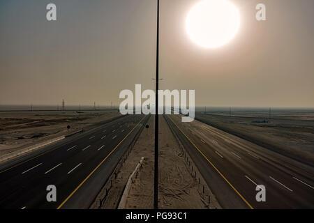 Mafraq-Ghweifat internationale Fernverkehrsstraße, Vereinigte Arabische Emirate. Die Höchstgeschwindigkeit von 160 km/h auf eine saubere, glatte und ebene 8-spurige Autobahn. Blick nach Osten. - Stockfoto