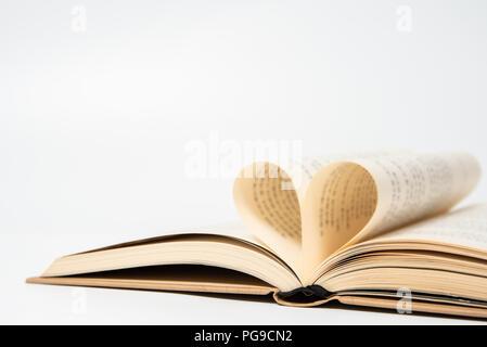 Nahaufnahme der geöffnete Buch mit Herz aus zwei Seiten geformt, auf weißem Hintergrund - Stockfoto