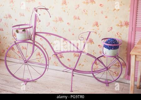 Rosa dekoratives Fahrrad auf rosa Hintergrund. Blume Wallpaper - Stockfoto
