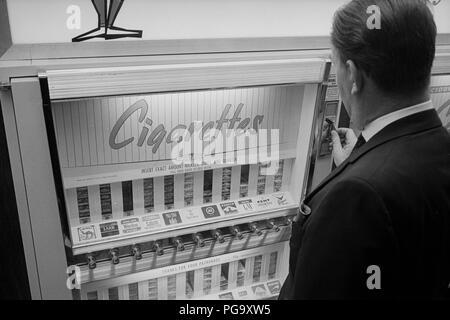 Ein Zigarettenautomat in einem Restaurant - 1964. Ein zigarettenautomat ist ein Automat, Cash in Zahlung für Packungen von Zigaretten. Automaten oft verzichten Packungen mit 12, 16 oder 18 Zigaretten, obwohl die Abmessungen der Verpackung die gleichen sind wie die entsprechenden Packung mit 20. - Stockfoto