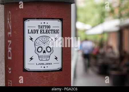 Ljubljana, Slowenien - 23. Juli 2018: Ansicht einer eisernen Säule mit einer Werbung Aufkleber für ein Tattoo Studio namens Lady Electric in Lubljana, Slovenien - Stockfoto