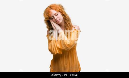 Junge rothaarige Frau schlafen müde Träumen und mit den Händen zusammen posieren während lächelnd mit geschlossenen Augen. - Stockfoto