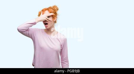 Junge rothaarige Frau peeking im Schock für Gesicht und Augen mit der Hand, schauen durch die Finger mit peinlich Ausdruck. - Stockfoto
