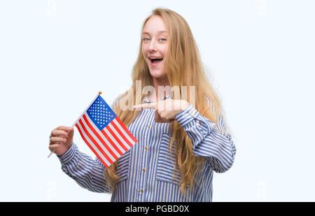 Blonde Teenager woman holding Flagge der Vereinigten Staaten von Amerika sehr glücklich zeigte mit Hand und Finger - Stockfoto