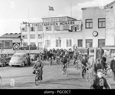 Werk in den 1950er Jahren. Arbeit ist für den Tag auf dem Fahrrad und Motorrad Monark in Schweden. Die Arbeiter verlassen die Fabrik gebäude auf ihre Fahrräder und Mopeds. Schweden 1958 - Stockfoto