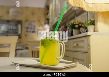 Limonade in ein Glas mit einem Handgriff über ein retro Innenraum Hintergrund - Stockfoto