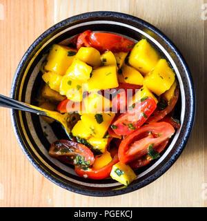 Mango und Tomaten Salsa (oder Salat) mit Minze chimichurri in einem schwarzen und weißen Schüssel auf einem Pinienwald Hintergrund, Schuß-legen. - Stockfoto