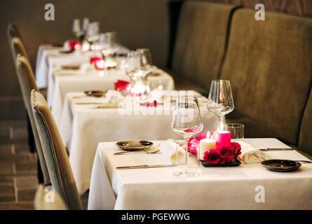 Romantische Tabelle Einstellungen in einem Restaurant mit mittelstücke von brennenden Kerzen und rote Rosen und elegante Glaswaren für ein intimes Abendessen für Zwei - Stockfoto