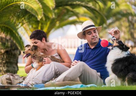 Schönes Mittelalter kaukasischen Paar sitzt auf dem Gras mit Palmen im Hintergrund beim Spielen mit zwei lustige und schöne Hunde und eine rote Kugel. Genießen Sie ein Stockfoto