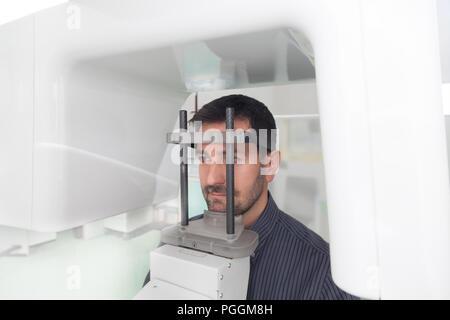 Junger Mann Portrait mit Panoramablick Digital X-ray seiner Zähne in der Zahnarztpraxis. - Stockfoto