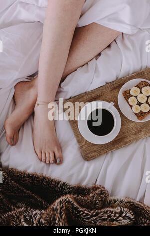 Nahaufnahme Beine einer Frau schlafen im Bett mit Frühstück durch ihre Seite. Frühstück mit Kaffee schwarz platziert neben eine Frau schlafend auf dem Bett. - Stockfoto