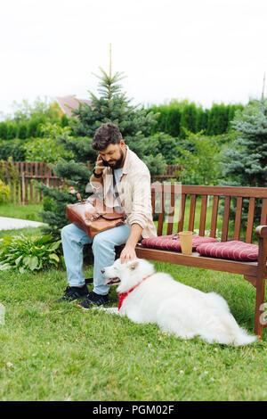 Dunkelhaarige Mann spielt mit seinem weißen Hund sitzt auf der Bank - Stockfoto