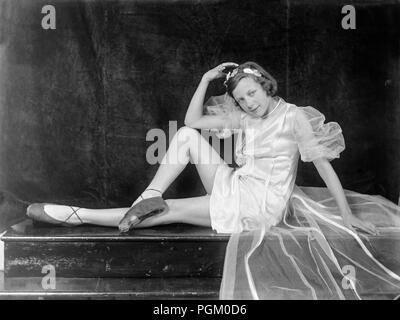 Anfang des zwanzigsten Jahrhunderts UK Foto von einem jungen Mädchen gekleidet wie eine Ballerina, für die Kamera posiert im Studio, reeling Sitzen auf einem Tisch. - Stockfoto