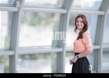 Moderne business Frau, die in der Nähe von einem großen Fenster im Büro. - Stockfoto