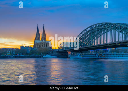 Hohenzollernbrücke mit dem Kölner Dom im Sonnenuntergang in Köln, Deutschland. - Stockfoto