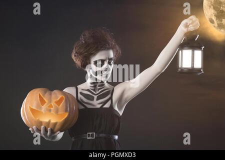 Frau Monster mit Kürbis und Laterne. Kreative dunklen Make-up, konzeptionelle Idee für Halloween. Unheimliche Alptraum in einem schwarzen Vampir, Band spi - Stockfoto