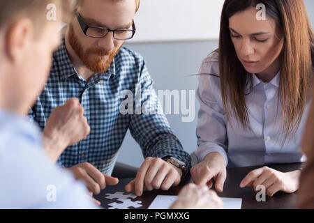 Konzentrierte sich Kolleginnen und Kollegen zusammensetzen Puzzle während der Konferenz - Stockfoto