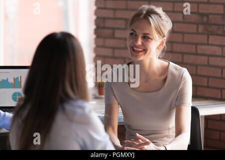 Lächelnd weibliche Angestellte, freundlich sprechen mit Kollegen - Stockfoto