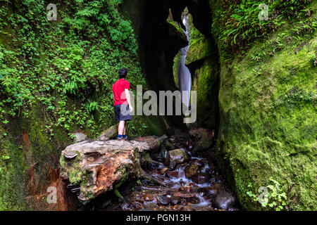 Wanderer erkunden Wasserfall in der Nähe von sombrio Beach, Juan de Fuca Provincial Park - in der Nähe von Port Renfrew, Vancouver Island, British Columbia, Kanada - Stockfoto
