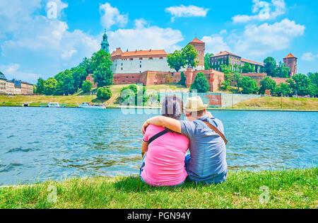 Das junge Paar sitzen auf der Bank von Vistule River mit Blick auf das Schloss Wawel in Krakau, Polen - Stockfoto
