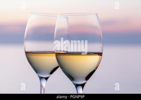 Zwei Gläser Weißwein gegen den Abendhimmel, close-up - Stockfoto