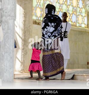TOUBA eine Enklave, SENEGAL - 26.April 2017: Unbekannter senegalesische Frau in traditioneller Kleidung Wanderungen mit einem Kind in der Großen Moschee von Touba eine Enklave, die Heimat der M - Stockfoto