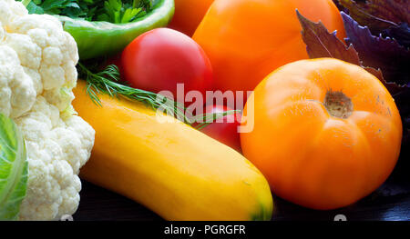 Buntes Gemüse Hintergrund. Reife Gemüse close-up. Tomaten, Blumenkohl, Zucchini, Paprika und Kräuter - Stockfoto