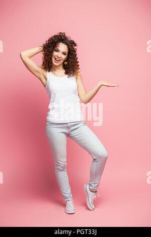 In voller Länge Porträt eines lächelnden Frau mit Copyspace auf dem Palm auf einem rosa Hintergrund isoliert. Mit Blick auf die Kamera. - Stockfoto