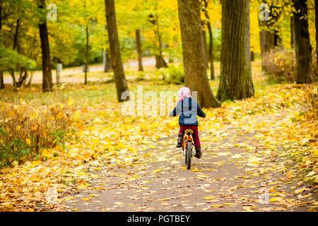 Kleines Mädchen auf einem Fahrrad im Park unterwegs mit Herbst Eiche und Ahorn bewachsen. Zurück Blick auf Kleines Kind in blue coat Fahrradfahren. Radfahrer im Herbst Park. Mädchen Radtouren im City Park Stockfoto