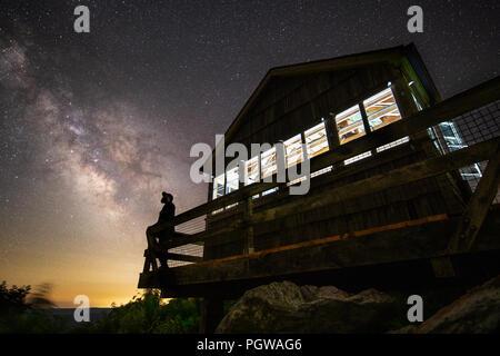 Ein Lone Star Gazer ist gegen die Milchstraße und einem dunklen Nachthimmel von der Plattform des alten Fire Tower am Hanging Rock Raptor Informationsstelle Silhouette - Stockfoto