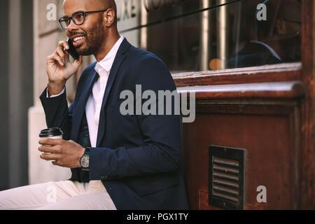 Happy afrikanischer Mann Entspannung im Freien mit Kaffee und Gespräch am Handy. Junger Mann in Anzug und Unterhaltung am Telefon sitzen. - Stockfoto
