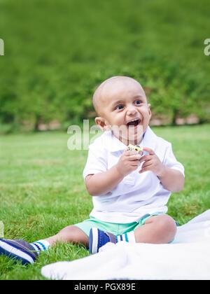 Portrait von cute adorable kleinen indischen South Asian baby boy im weißen Hemd sitzt auf dem Boden mit Spielzeug in Park Green Grass Decke draußen auf hell - Stockfoto