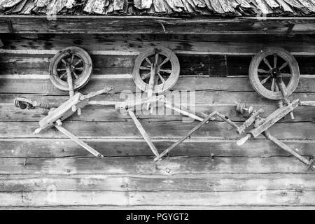 Vintage traditionelle Alte hölzerne durchdrehende Räder auf der hölzernen Wand der Ställe. - Stockfoto