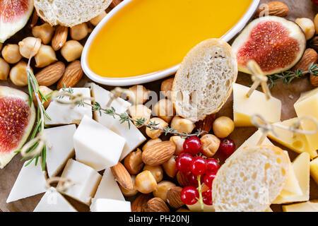 Käseplatte. Käse mischen mit Baguette Croutons, rote Johannisbeere, süsse Feigen-, Mandel-, Honig auf Holztisch. Verkostung Teller auf eine Holzplatte. Essen für den Wein. Ziegenkäse, Parmesan, Gouda - Stockfoto