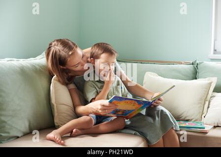 Junge Mutter, ein Buch zu lesen, ihr Kind, junge im Wohnzimmer ihre Heimat, Sonnenstrahlen durch das Fenster des - Stockfoto