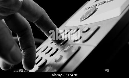 Nahaufnahme der Finger eines Menschen aus und wählen auf dem Festnetz Telefon Drücken der Zifferntasten auf dem Tastenfeld in ein Kommunikationskonzept. - Stockfoto