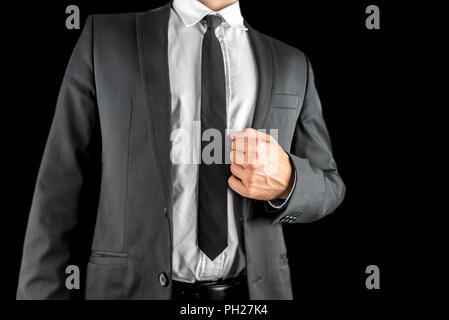 Nahaufnahme der Torso einer zuversichtlich Geschäftsmann im Anzug Holding das Revers seines stilvolle Jacke in der Hand konzeptionelle von Erfolg und Selbst-assuranc - Stockfoto