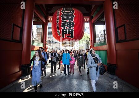 Touristen vorbei unter dem riesigen roten Chochin Laterne an die Kaminarimon Präfektur Tor (Donner Tor) der Sensoji-Tempel in Asakusa, Tokyo, Japan, November 10, 2017. () - Stockfoto