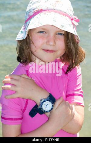 Junge Mädchen tragen (Sonnenhut) bis 6 Jahre/6 Jahr alt ist ihr Vati/Vater mit Uhr/Zeit Stück am Strand an einem sonnigen Tag mit blauen Himmel tragen. (101) - Stockfoto